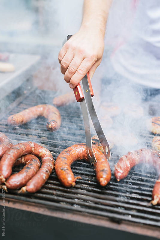 Cook grilling sausages by Pixel Stories for Stocksy United