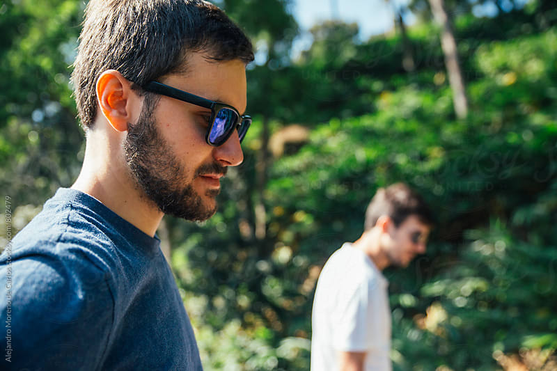 Sideways profile of two young men with sunglasses looking down in a forest on a sunny day by Alejandro Moreno de Carlos for Stocksy United