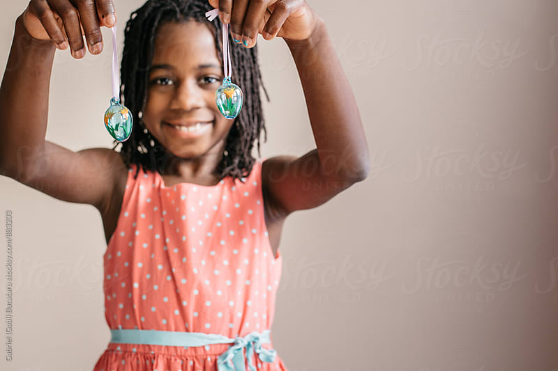 Smiling black girl holding two Easter egg decorations by Gabriel (Gabi) Bucataru for Stocksy United