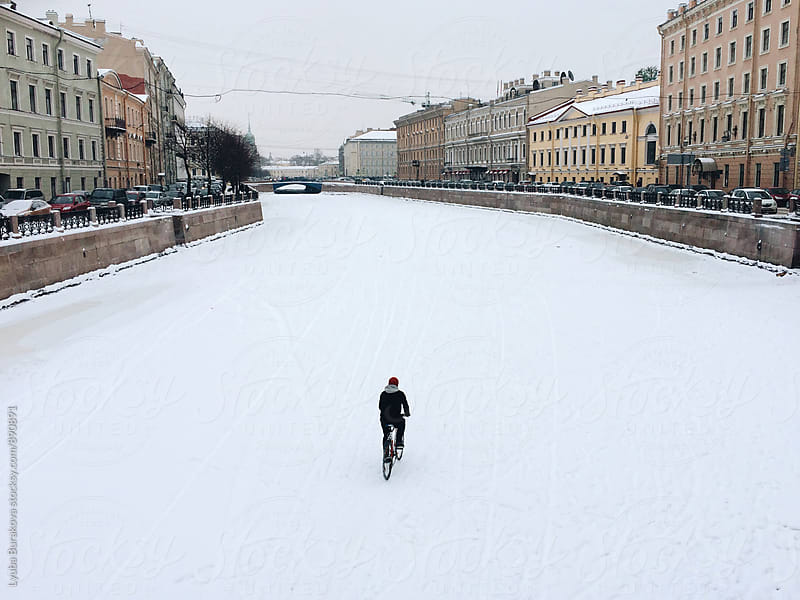 Man riding a bicycle on frozen riverbed  by Lyuba Burakova for Stocksy United
