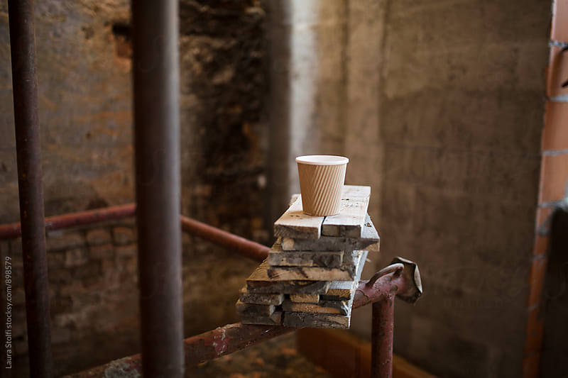 Paper coffee cup on top of wooden boards on building site by Laura Stolfi for Stocksy United