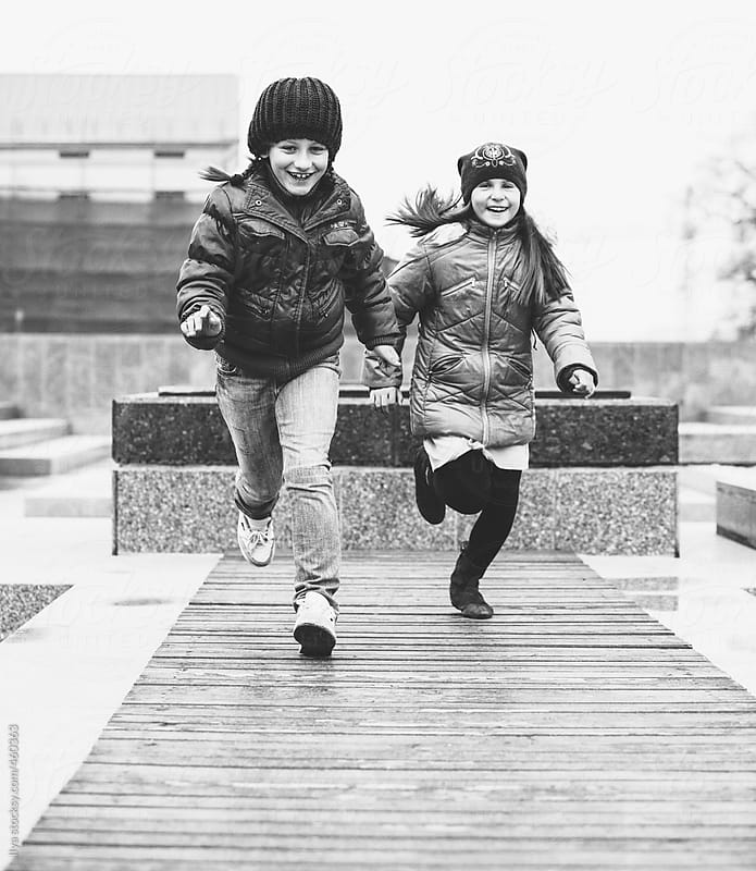 Two young happy children (girls) playing in the city together monochrome by Ilya for Stocksy United