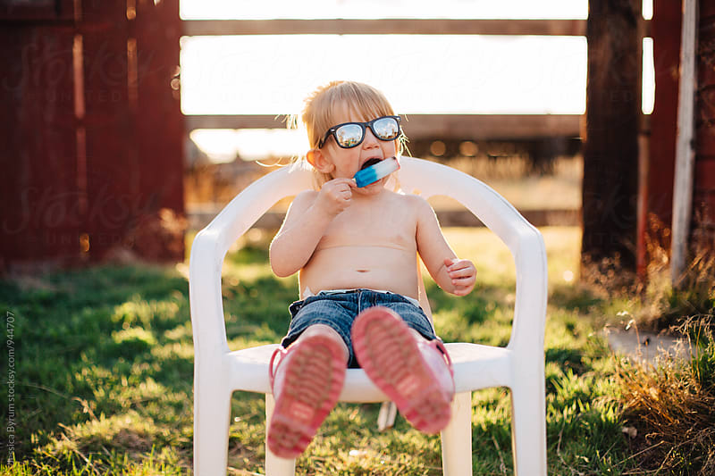 Little girl wearing sunglasses eating popsicle by Jessica Byrum for Stocksy United