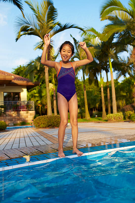lovely little asian girl ready to jump to the swimming pool by cuiyan Liu for Stocksy United