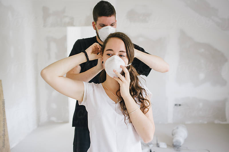 Girl is putting her dust mask on by Tomas Mikula for Stocksy United