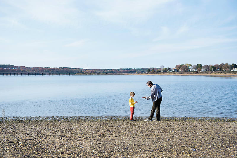 Father teaches son how to skip rocks by Cara Dolan for Stocksy United