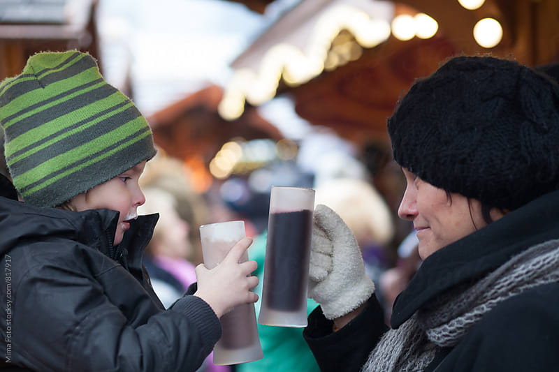 Mother and son drinking hot drinks at Christmas Market by Michael Zwahlen for Stocksy United
