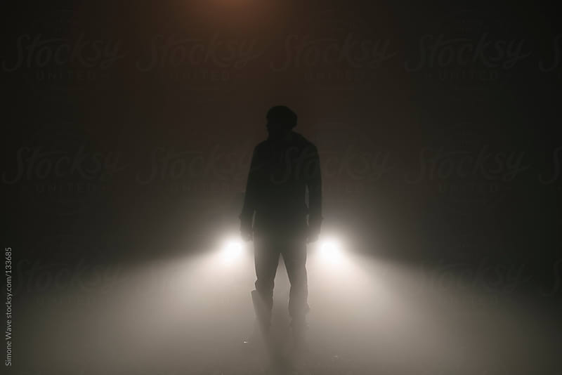 Man standing in the fog against car lights  by GIC for Stocksy United