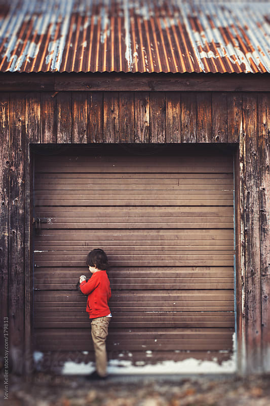 Young Boy Trying to Open an Old Garage Door by Kevin Keller for Stocksy United