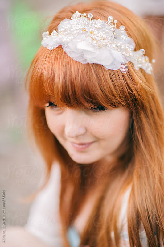 Portrait of a young beautiful redhead woman with long hair and green eyes with a tiara by Adrian Cotiga for Stocksy United