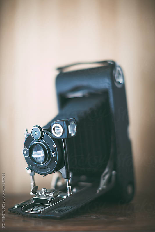 Antique film camera on wooden table. by BONNINSTUDIO for Stocksy United