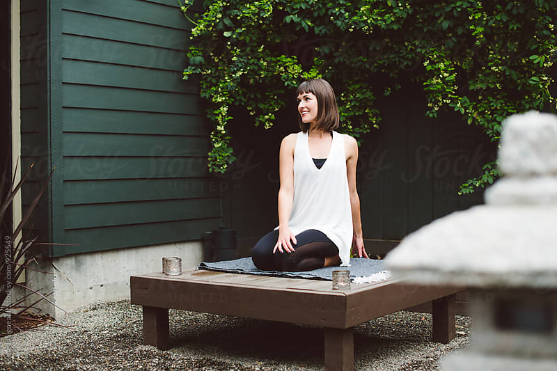 Young woman in seated twist outside in garden. by Kate Daigneault for Stocksy United