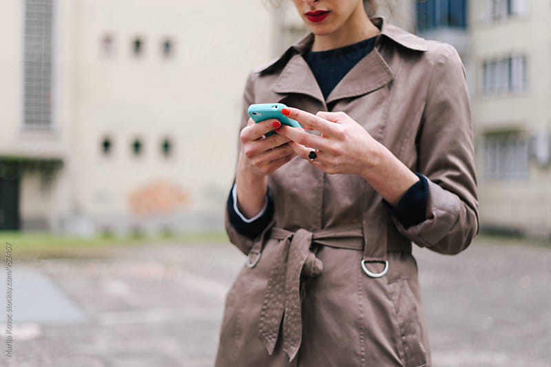 Female hands holding a smart phone by Marija Kovac for Stocksy United