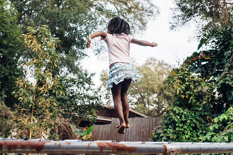 African American girl on a trampoline by Gabriel (Gabi) Bucataru for Stocksy United