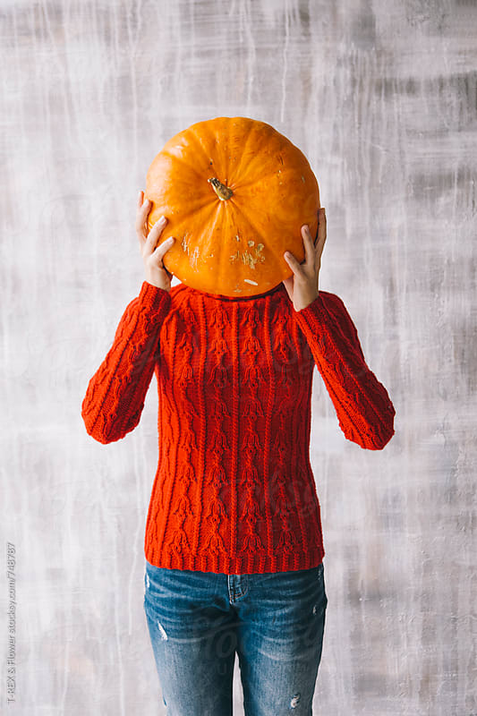 Woman holding pumpkin in front of face by Danil Nevsky for Stocksy United