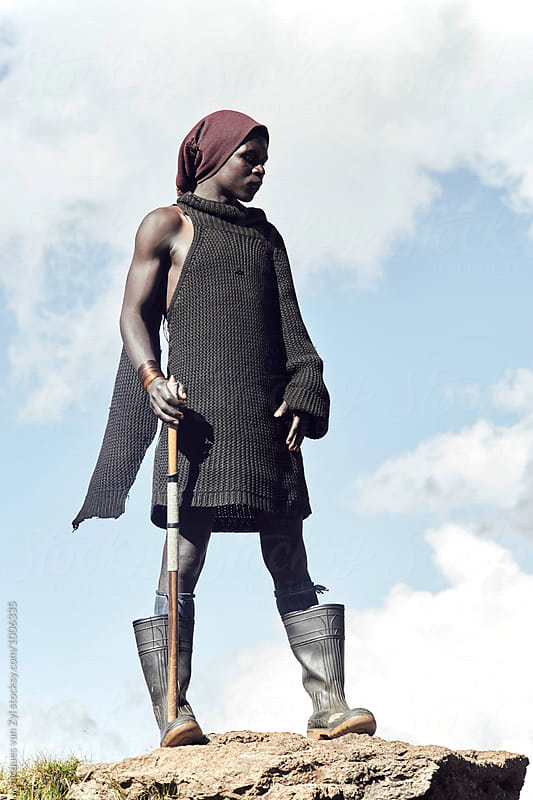 A Portrait of a young black Basotho  shepherd standing against a clouded sky.  by Jacques van Zyl for Stocksy United