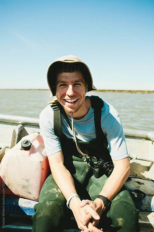 Happy fisherman sitting on a boat by Kristine Weilert for Stocksy United