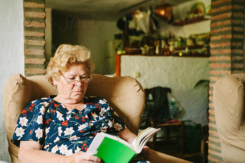 Senior woman reading in her living room.  by kkgas for Stocksy United