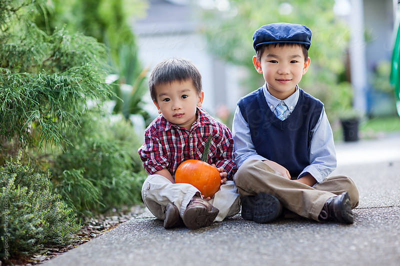 Asian boys holding a pumpkin by Suprijono Suharjoto for Stocksy United