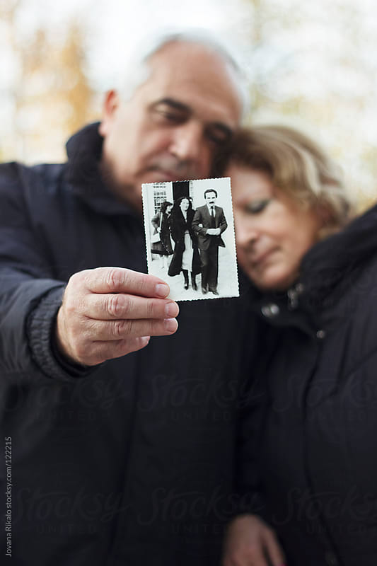Older man holding a photo of him and his wife from younger days by Jovana Rikalo for Stocksy United