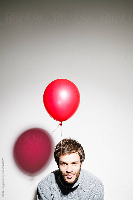 Studio portrait of a handsome young man with red balloon by Nabi Tang for Stocksy United