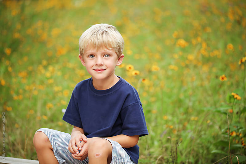 portrait of a boy sitting in front of wild flowers by Kelly Knox for Stocksy United