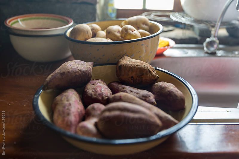 Bowls of sweet and yellow potatoes on a rustic kitchen bench by Ben Ryan for Stocksy United