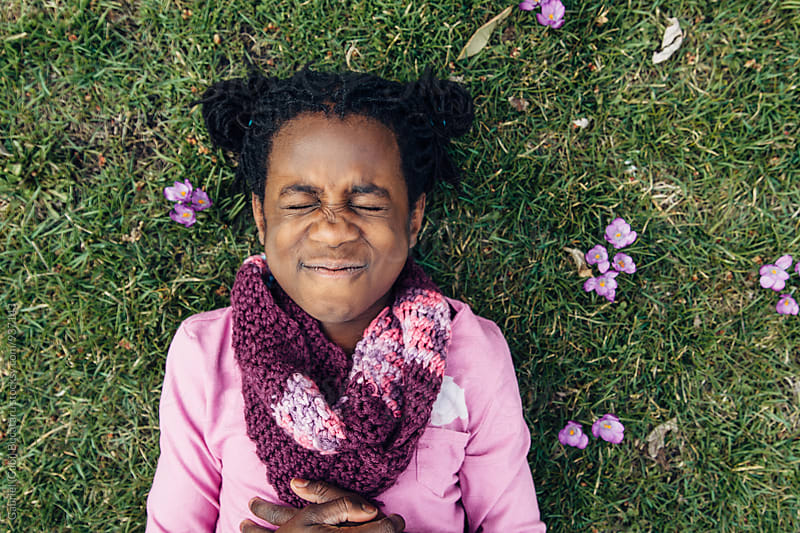 Silly black girl with closed eyes laying on grass with crocus flowers by Gabriel (Gabi) Bucataru for Stocksy United