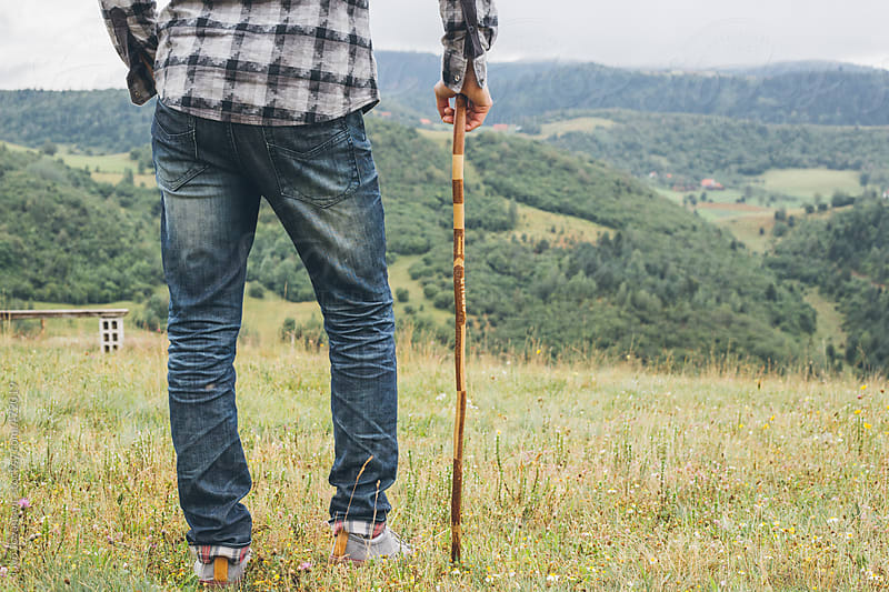 Young man wearing jeans, hicking  with his walking stick in the mountains by Jovo Jovanovic for Stocksy United
