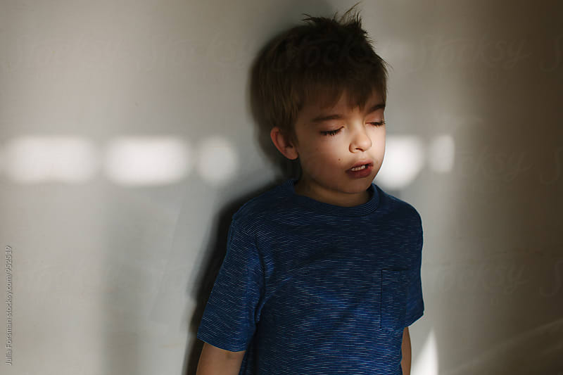Young boy standing against wall in early morning light in a house. by Julia Forsman for Stocksy United