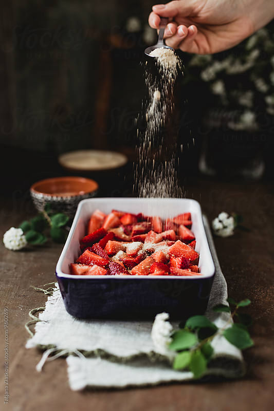 Making strawberry crumble by Tatjana Zlatkovic for Stocksy United