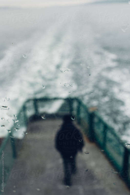 Man Standing On Ferry Deck Through Window View With Raindrops by Luke Mattson for Stocksy United