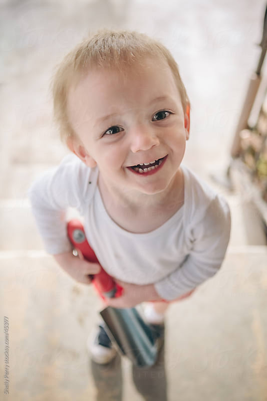 Two Year Old Boy with Big Expression holding a Hand Trowel, Dirty from Helping in the Yard by Shelly Perry for Stocksy United