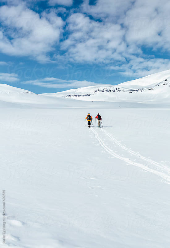 Two skiers touring in the mountains of Iceland by Soren Egeberg for Stocksy United