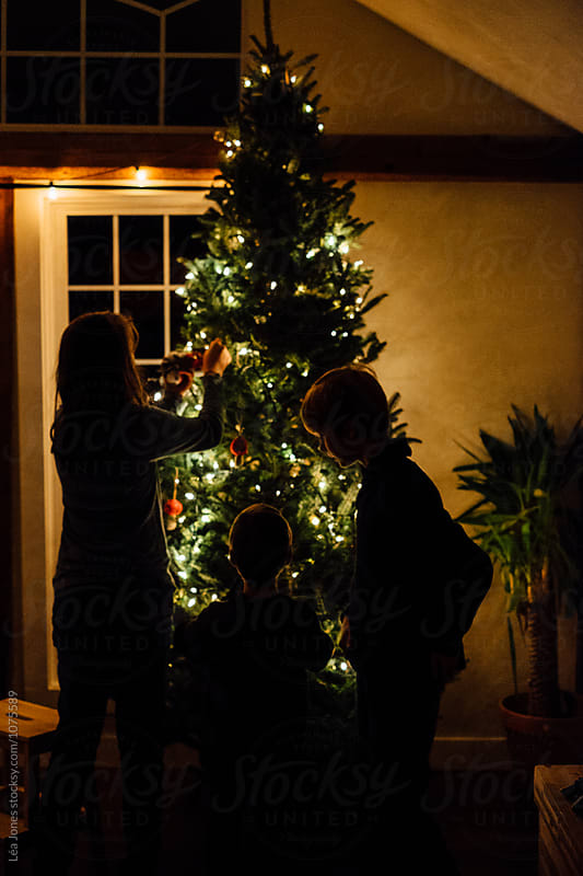 children putting ornaments in christmas tree by Léa Jones for Stocksy United