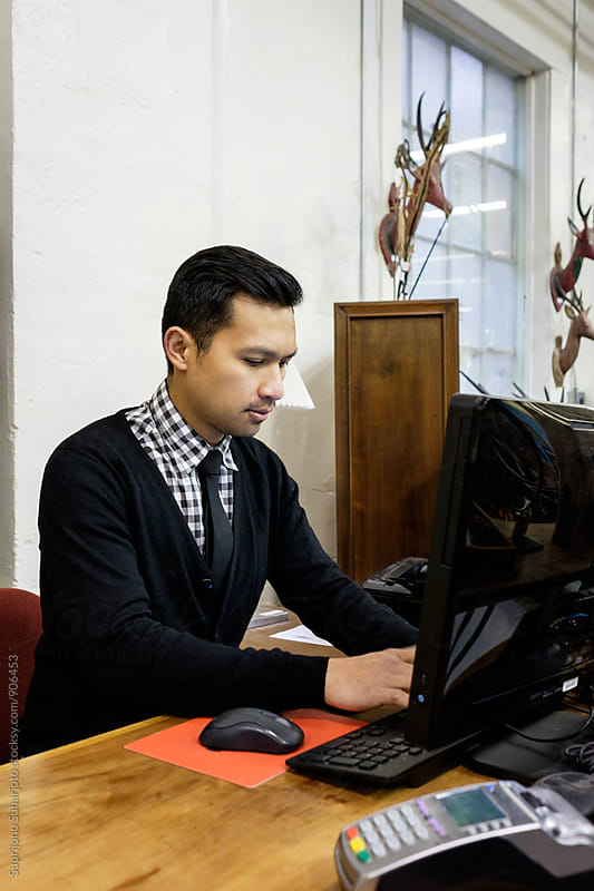 Small business owner working on his computer at his furniture store by Suprijono Suharjoto for Stocksy United