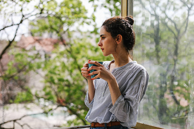 Young brunette holding a cup of a coffee by Marija Kovac for Stocksy United