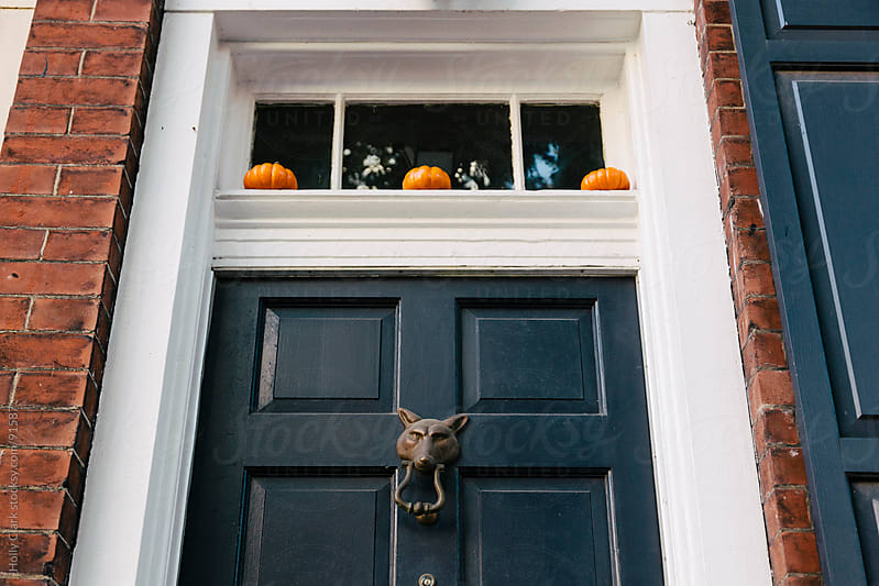 Three tiny pumpkins decorate a front door. by Holly Clark for Stocksy United