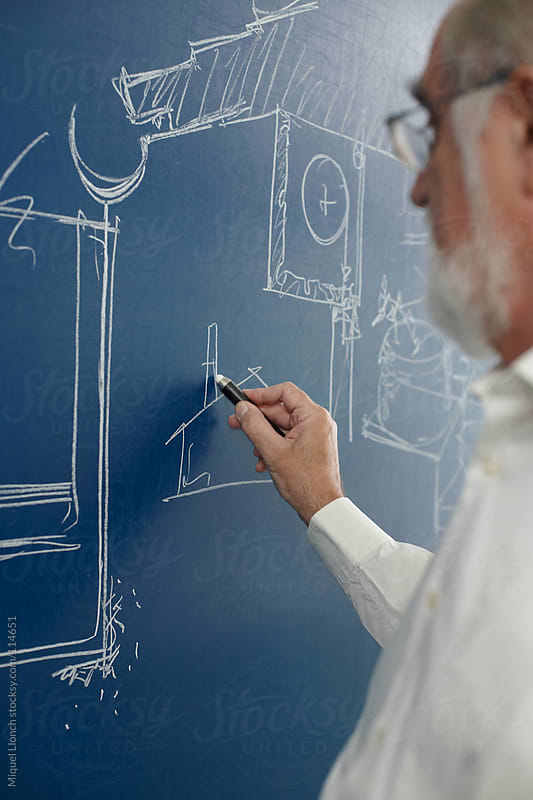 Mature professor drawing on a blue blackboard with chalk by Miquel Llonch for Stocksy United