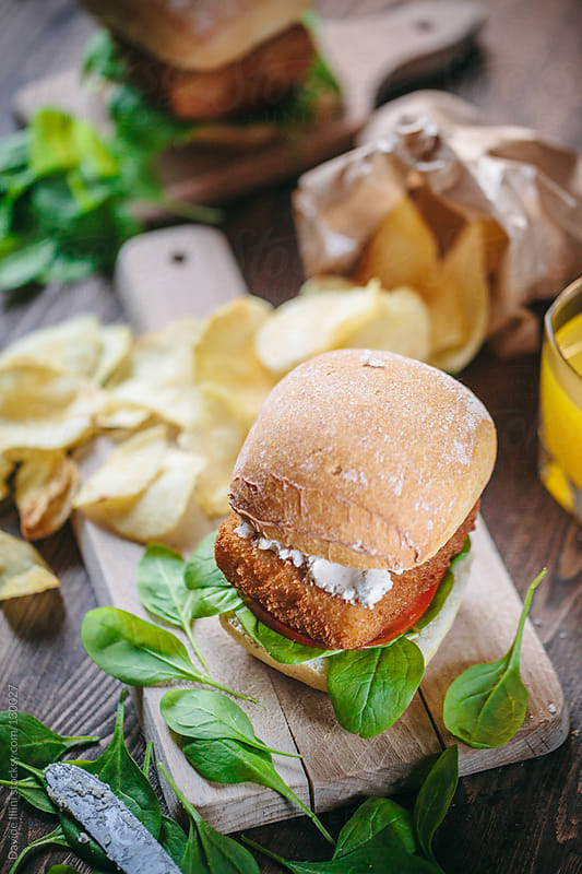 Fish burger with chips by Davide Illini for Stocksy United