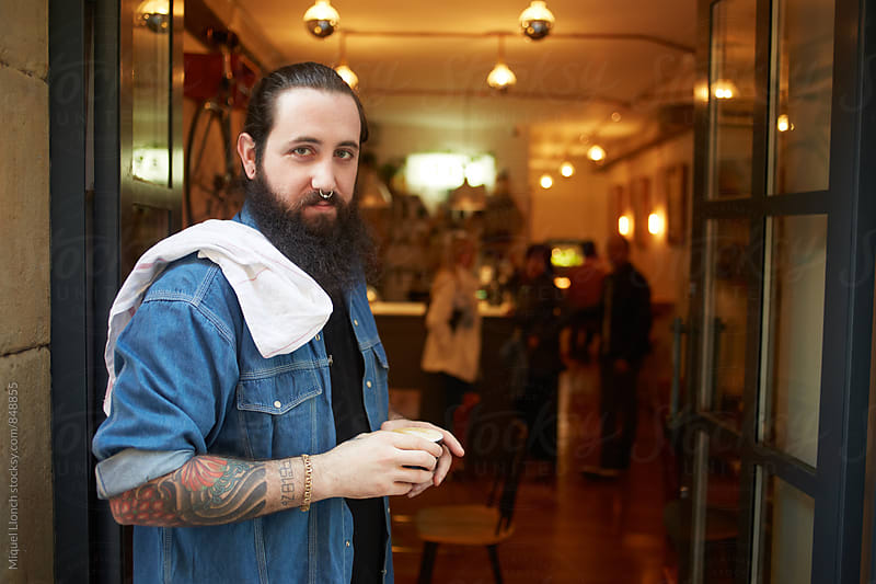 Bartender with a cup of coffee at the door of his business by Miquel Llonch for Stocksy United