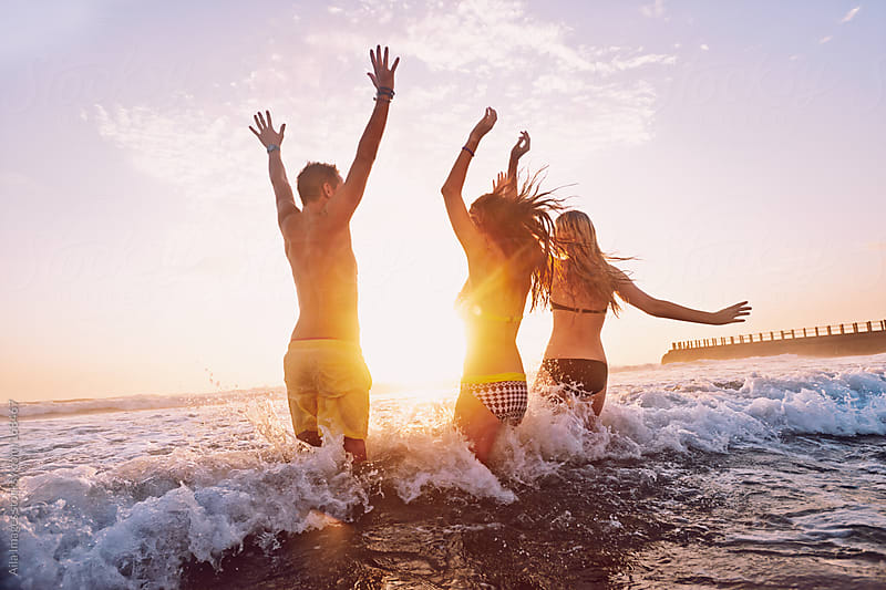 Three Friends swimming in the sea at Sunrise by Aila Images for Stocksy United