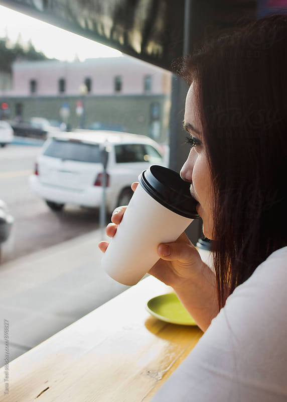 young woman enjoys coffee in cafe by Tana Teel for Stocksy United