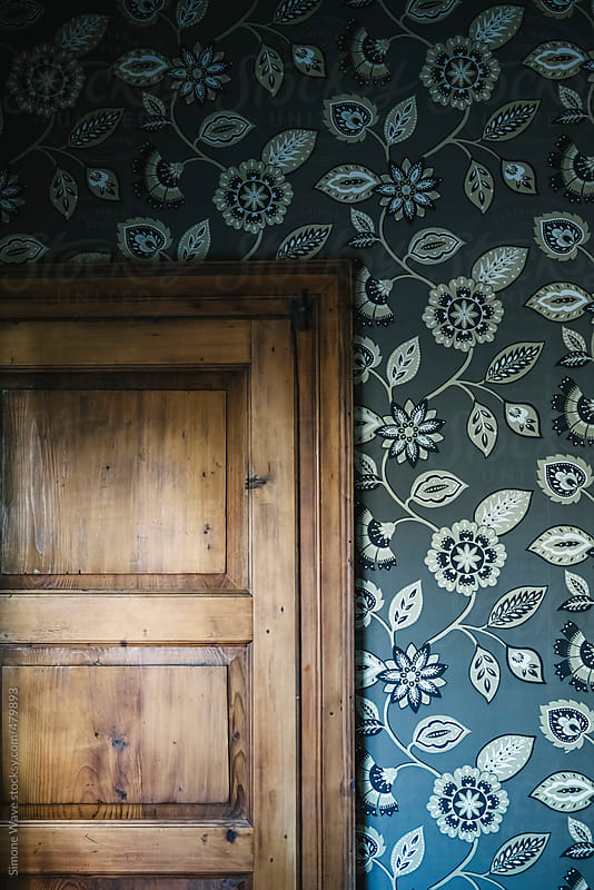 Flower wallpaper and wooden door by GIC for Stocksy United
