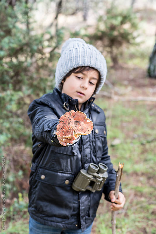 Child showing a mushroom freshly caught carrying some binoculars and a stick by Marta Muñoz-Calero Calderon for Stocksy United