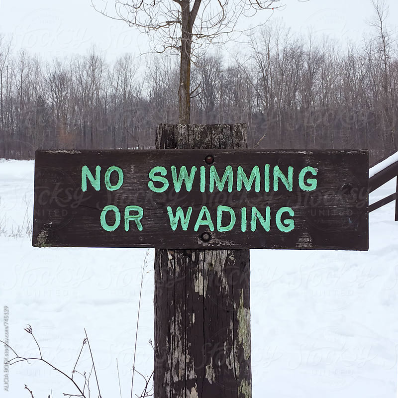 A No Swimming Sign On The Edge Of A Frozen Pond by ALICIA BOCK for Stocksy United
