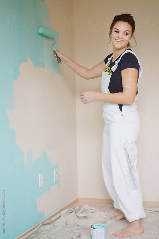 Young woman rolls paint on a wall by Tana Teel for Stocksy United