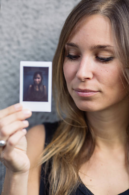 Young woman holding her Polaroid portrait by Alberto Bogo for Stocksy United