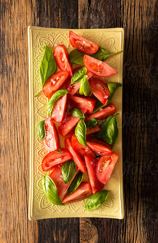 Tomato Salad with Basil on Rustic Wood  by Jeff Wasserman for Stocksy United
