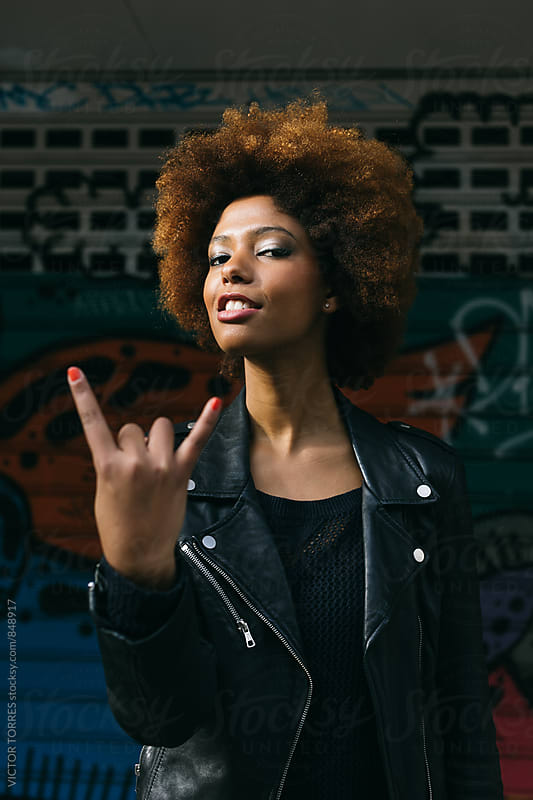Young Latin Woman Doing the Rock Sign by Victor Torres for Stocksy United